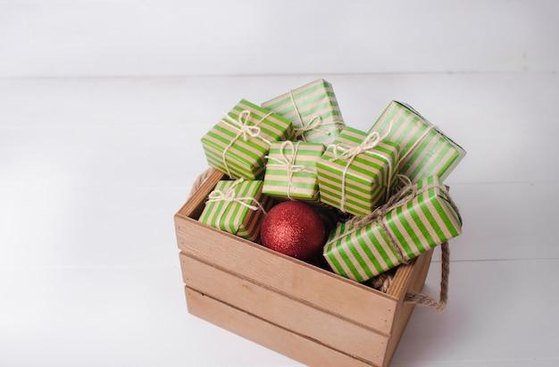 Sfondo di natale con scatole regalo e ramo di pino su uno sfondo di legno bianco.