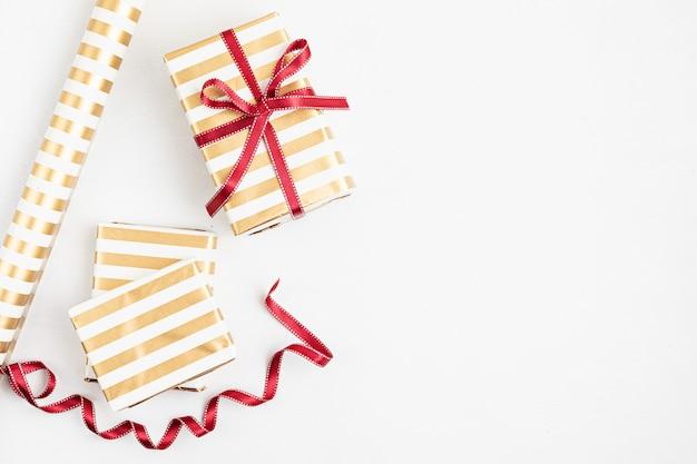 Sfondo di natale con scatole regalo, nastro, rotoli di carta e ornamento di natale