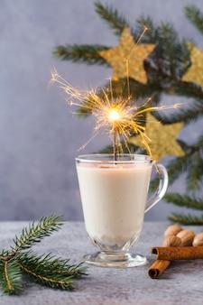 Sfondo di natale con, scatole regalo, stelle, decorazioni festive, abete, bastoncini di cannella, bevanda calda allo zabaione.