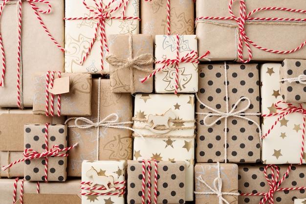 Sfondo di natale con scatole regalo avvolte in carta kraft marrone distesa piatta.