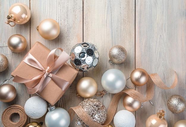 Sfondo di natale con un regalo decorazioni natalizie e nastri su uno sfondo chiaro