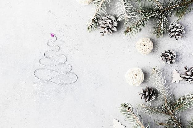 Sfondo di natale con regali, rami di abete, coni e neve sul tavolo di cemento grigio. composizione di natale. disposizione piatta. vista dall'alto