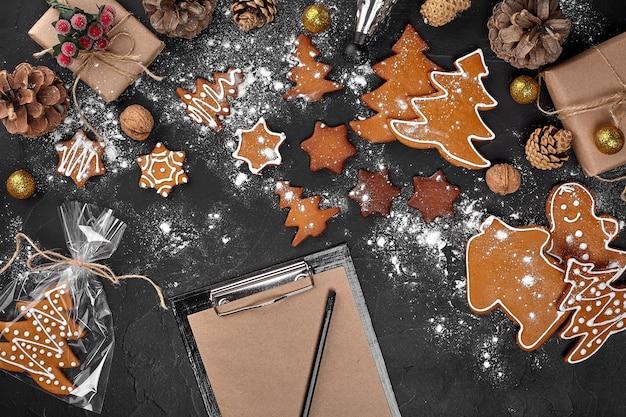 Sfondo di natale con biscotti di panpepato e fogli di carta artigianale. copia spazio. vista dall'alto