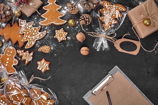 Sfondo di natale con biscotti di pan di zenzero e fogli di carta artigianale per copia spazio