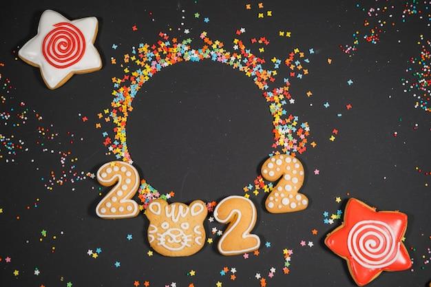 Sfondo di natale con pan di zenzero sullo spazio della copia di vista superiore della carta di umore di festa di superficie grigia