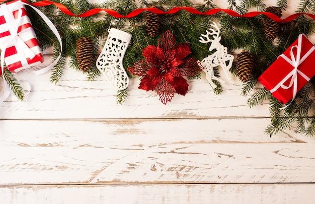 Sfondo natalizio con rami verdi di abete rosso, coni, regali festivi in confezione rossa e un fiore rosso tradizionale. una copia dello spazio.