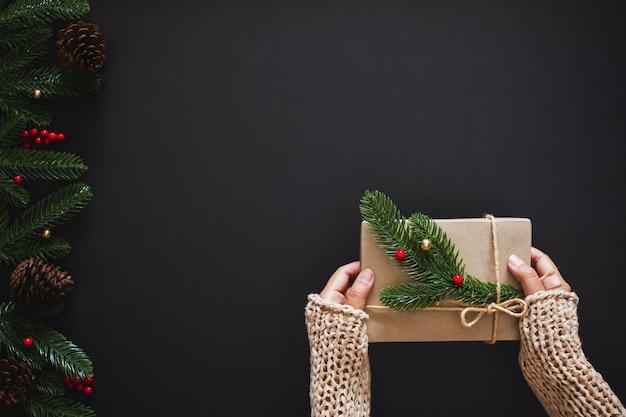 Sfondo di natale con la mano che tiene il regalo presente per natale e felice anno nuovo concetto