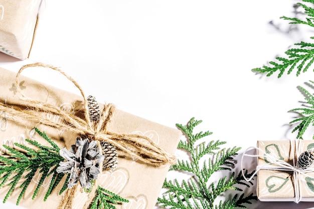 Sfondo natalizio con scatole regalo artigianali, bugne di corda e decorazioni con pigne e twigson bianco. preparazione per le vacanze, copy spase.