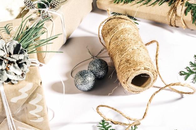 Sfondo natalizio con scatole regalo artigianali, bugne di corda e decorazioni con pigne e twigson bianco. preparazione per le vacanze...