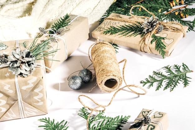 Sfondo natalizio con scatole regalo fatte a mano, bugne di corda e decorazioni con pigne e twigson bianco. preparazione per le vacanze.