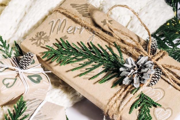 Sfondo di natale con scatole regalo fatte a mano, bugne di corda e decorazioni con pigne e twigson su fondo di legno. preparazione per le vacanze. fatto a mano. messa a fuoco selettiva.