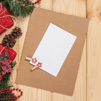 Sfondo di natale con decorazioni natalizie e carta, bacche rosse, ramo di abete e regali vista dall'alto