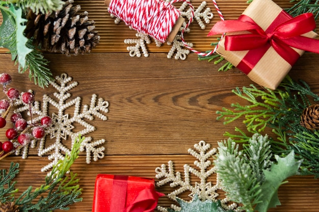Sfondo di natale con scatole regalo rosse, rami di abete e decorazioni invernali.