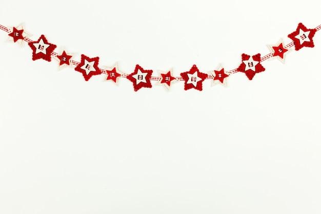 Sfondo di natale con corona rossa di stelle.