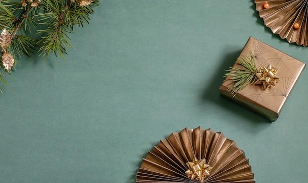 Sfondo di natale con ventaglio di carta scintillante, scatola confezionata presente e ramo di un albero di natale. regali ecologici fatti a mano, concetti fai-da-te. vista dall'alto, foto piatta con copia spazio.