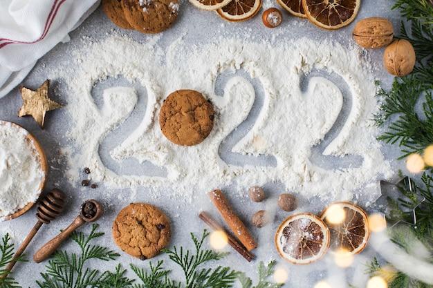 Sfondo di natale con biscotti alle spezie e numero dipinto sulla farina felice anno nuovo