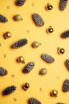 Sfondo di natale con giocattoli ornamenti natalizi in oro su sfondo giallo