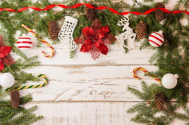 Sfondo di natale con decorazioni natalizie tradizionali: palline di vetro, canna di caramello, fiore rosso su fondo di legno bianco. una copia dello spazio.