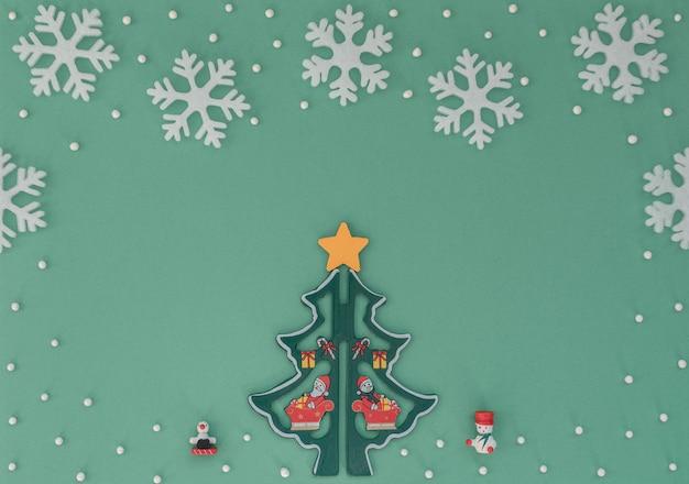 Sfondo di natale con albero di natale in legno, fiocchi di neve bianchi, decorazioni