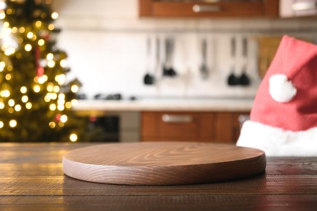 Sfondo di natale con piano d'appoggio in legno, cappello da babbo natale e cucina sfocata.