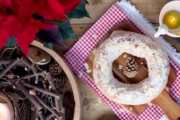 Natale prodotti da forno su un tavolo e un fiore con foglie rosse, candele