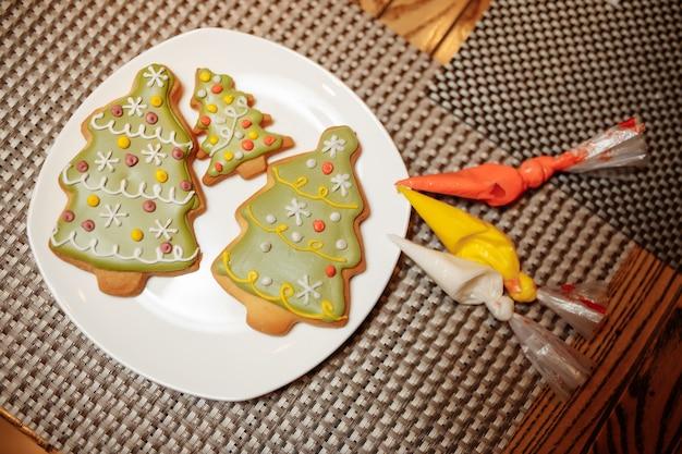Amici del forno di natale che decorano i biscotti di pan di zenzero appena sfornati con glassa