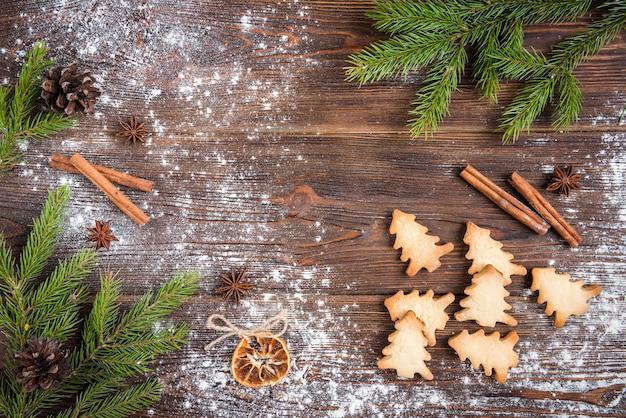 Cottura natalizia di biscotti allo zenzero su legno scuro con rami di abete.