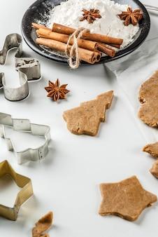 Cottura natalizia. pasta allo zenzero per pan di zenzero, panpepato, stelle, alberi di natale, mattarello, spezie (cannella e anice), farina. sul tavolo di marmo bianco della cucina di casa. copia spazio