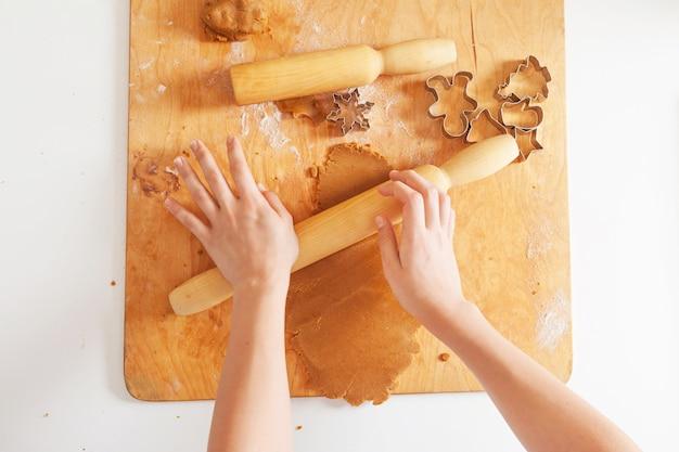 Cottura natalizia. mani di ragazze che producono i biscotti. pasta allo zenzero per pan di zenzero, formine per biscotti, farina su tavola di legno.