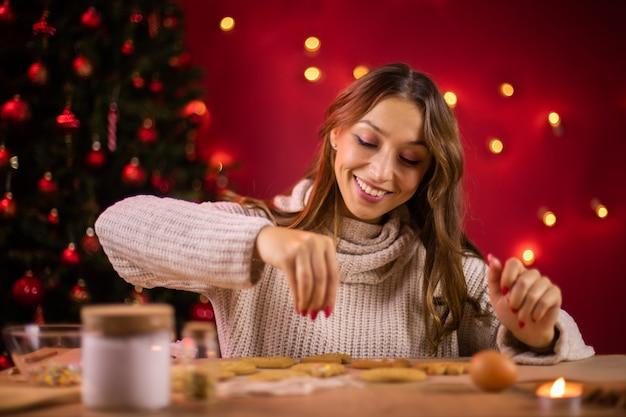 Cottura natalizia. la donna sorridente prepara i biscotti allo zenzero nell'accogliente atmosfera di capodanno, divertiti durante le vacanze invernali a casa. laboratorio di cucina artigianale da forno, concetto di tradizione natalizia.