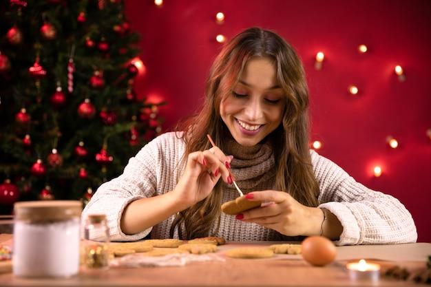 Cottura natalizia. giovane donna graziosa che fa la decorazione dei biscotti di natale per la cena in famiglia di capodanno, divertiti durante le vacanze invernali a casa. dolci da forno artigianali, tradizioni lavorative stagionali