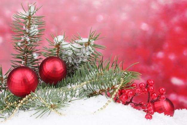 Palla di natale e albero verde nella neve su rosso Foto Premium