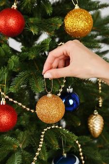 Palla di natale in mano sullo sfondo dell'albero di natale