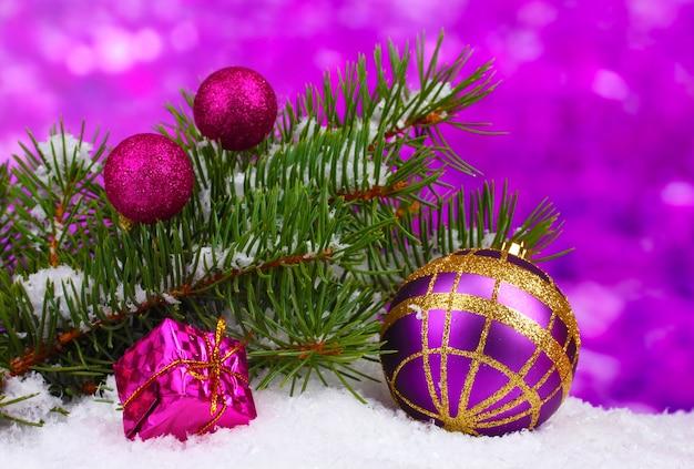 Palla di natale e giocattolo con albero verde nella neve su viola