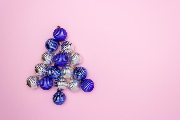 Palle di natale per decorare blu e argento su uno sfondo rosa a forma di albero di natale