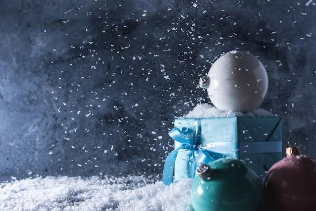 Palle di natale e confezione regalo su sfondo blu neve