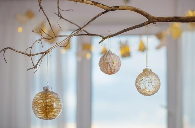 Palle di natale sul ramo d'oro sulla finestra di sfondo