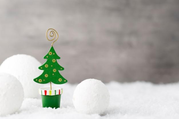 Palle di natale, biglietto di auguri e abete sulla neve
