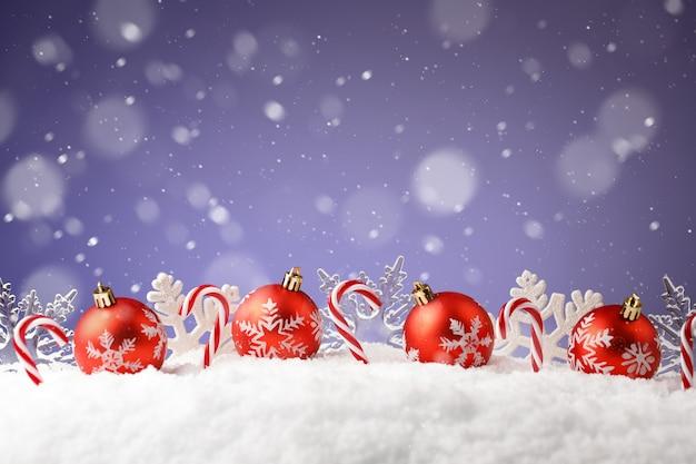 Palle di natale, fiocchi di neve e caramelle in un cumulo di neve