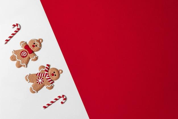 Banner di natale omino di pan di zenzero con bastoncino di zucchero su sfondo bianco con spazio rosso