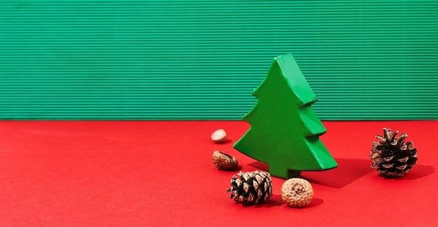 Banner di natale di confezione regalo verde e pigne. albero di natale in colori tradizionali e ombre dure