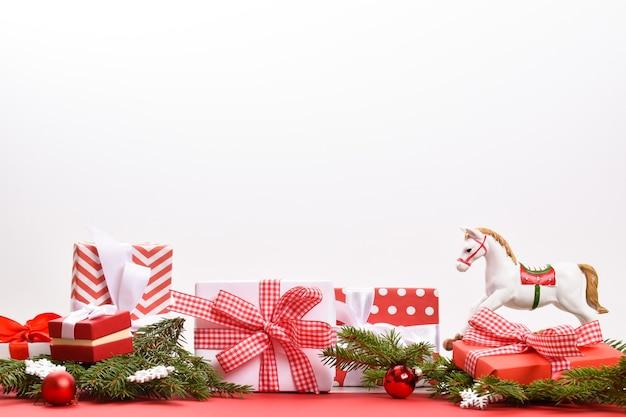 Uno striscione natalizio con regali un ramo di abete e un cavallo