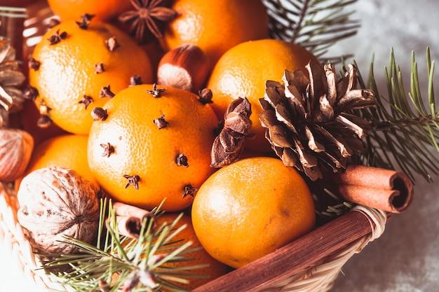 Cesto di natale - abete, mandarini e spezie sotto la neve
