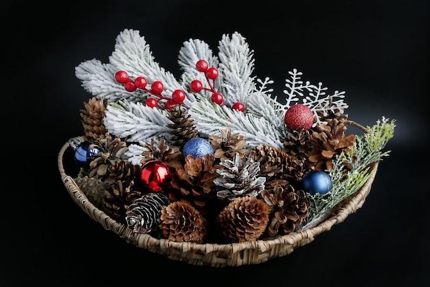 Cesto natalizio con coni, palline decorative colorate e ramo di conifere ricoperto di neve su uno sfondo scuro.