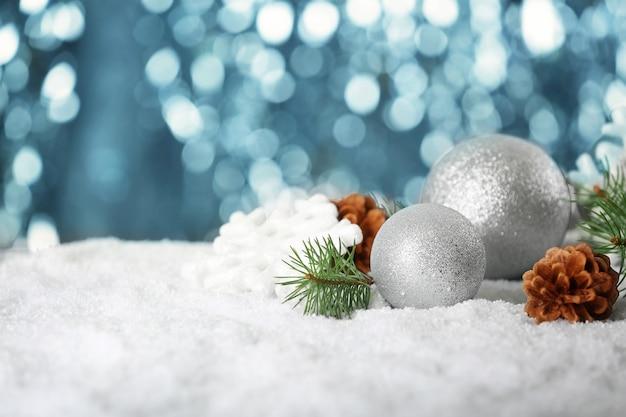 Cono di palline di natale e ramo di conifere sulla neve contro luci sfocati