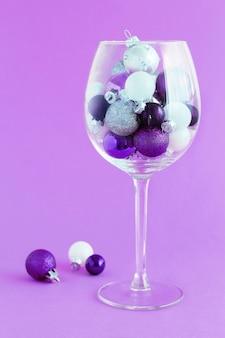 Bagattelle di natale in un bicchiere di vino su uno sfondo viola