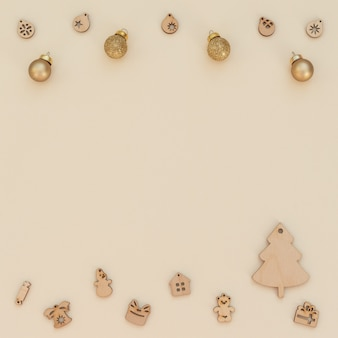 Sfondo natale beige con decorazioni natalizie in legno e palle di natale dorate. stile piatto laici con spazio di copia. biglietto di auguri di capodanno.