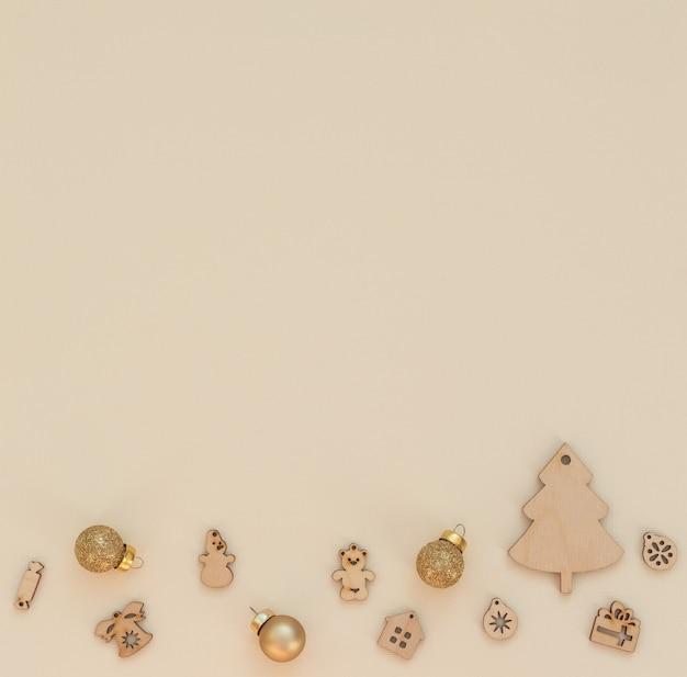 Sfondo natale beige con decorazioni natalizie in legno e palle di natale dorate. stile piatto laici con spazio di copia.