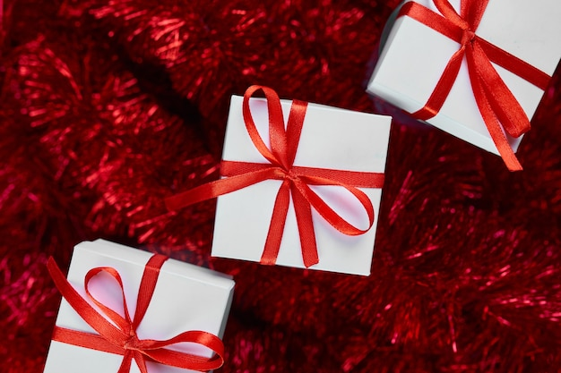 Scatola regalo nera di natale su sfondo rosso tinsel decorazioni abbondanti vista dall'alto piatta