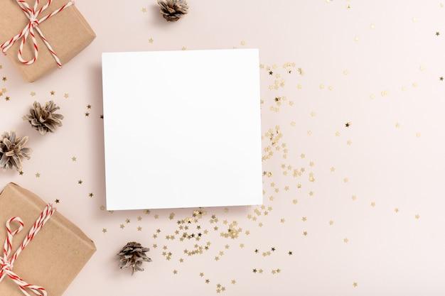 Natale. mockup di carta quadrata vuota, coriandoli di stelle dorate, protuberanze, scatole regalo su sfondo beige